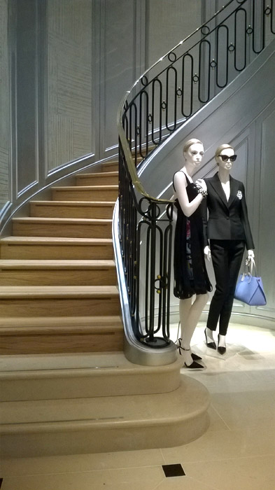 Christian Dior shop mannequins standing next to metal stair balustrade in London shop.