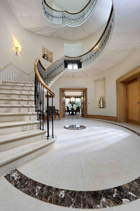 A grand house entrance hall with a marble staircase and wrought iron balustrade.
