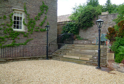 A stone built house in Wales with simple wrought iron balustrade and railings for stone steps illuminated at night by ironwork lamps