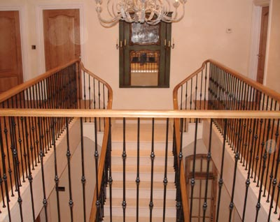 Eurpean oak handrail on this marble clad staircase with forged wrought ironwork balustrade