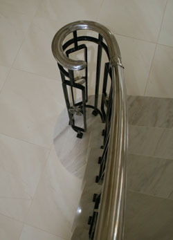 Shaped steel balustrading formed into a monkey tail newel post