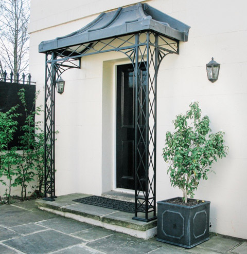 Traditional Regency Period hand crafted Trellis style Ironwork side entrance Porch Portico with Cast Aluminium shoes and sunray Gallows Brackets and covered with a Curved and Hipped Canopy Roof frame