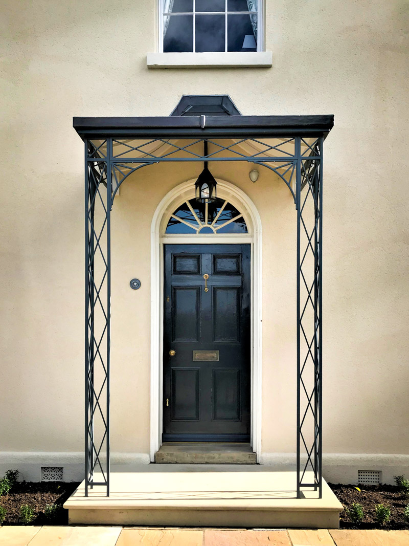 Wrought Iron Regency trellis design porch or portico covering a Georgian front door with traditional curved roof frame lined and covered in lead.
