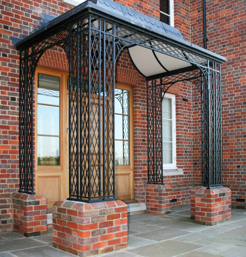 Large trellis style front Entrance Ironwork Porch on Brick with Custom Lead Roof Frame and spandrel Brackets