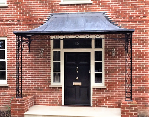 Traditional Blacksmith made Regency Style Modern large Metal Porch on Brick Piers with Lead Covered Roof Frame and Cast Iron Shoe Covers over a Large front door on a substantial brick home