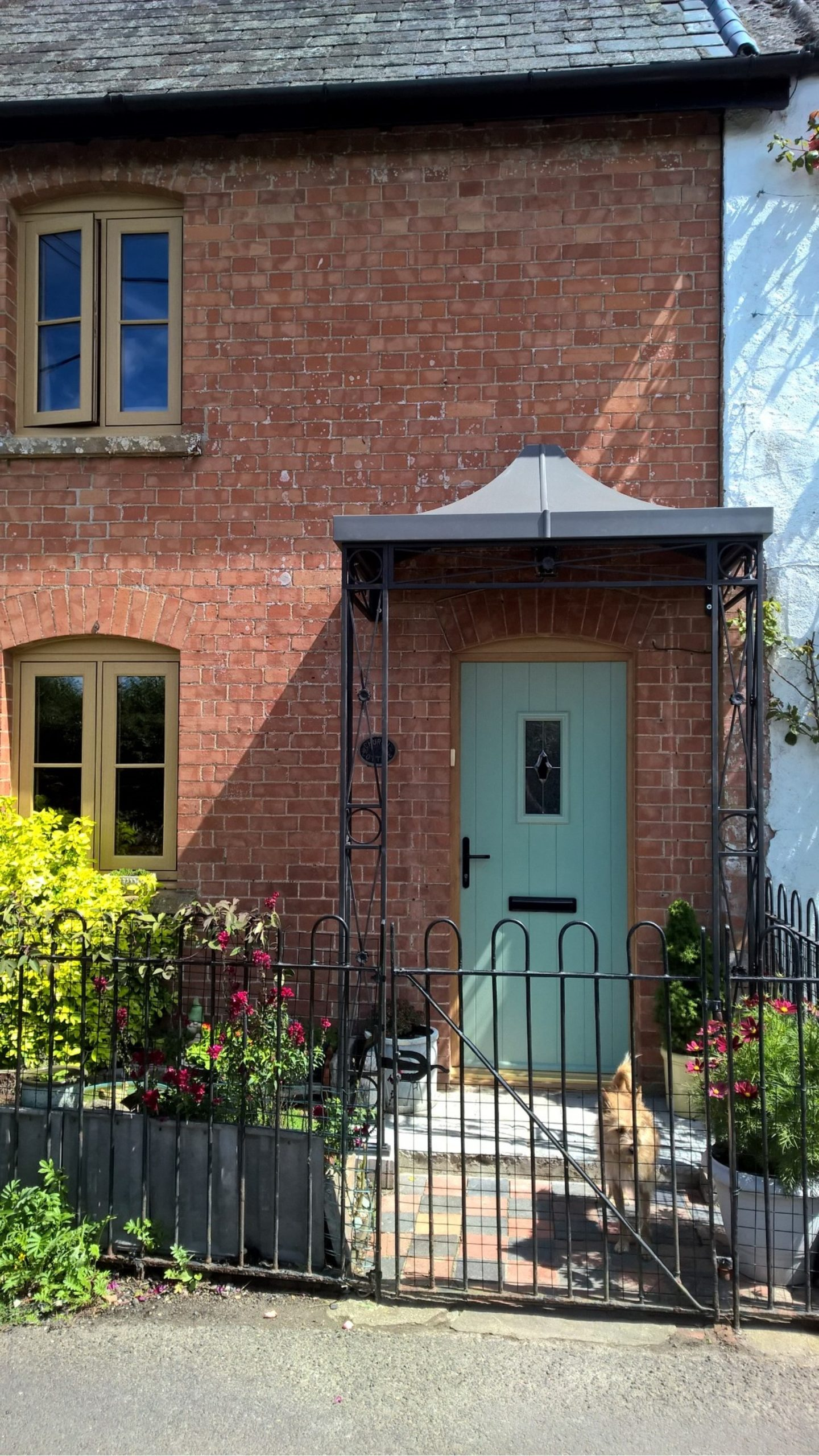A traditional hand crafted Deco Style wrought iron Porch portico awning featuring decorative central flower detail and cast shoe covers finished with a complete roof formed from zinc galvanised mild steel which is powder coated in a heritage lead grey colour