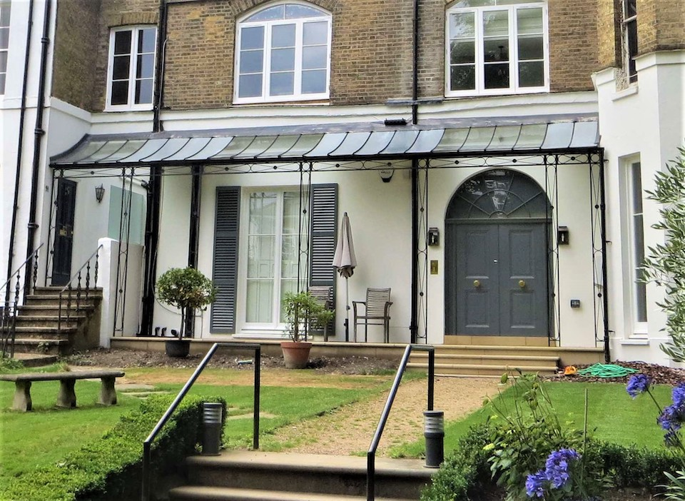 Traditional Metal Decorative Wrought Iron Verandah with infinity pattern and central cast flower detail and a curved Glazing Bar Roof, glass panels over windows and doors with zinc infill sheets to remainder