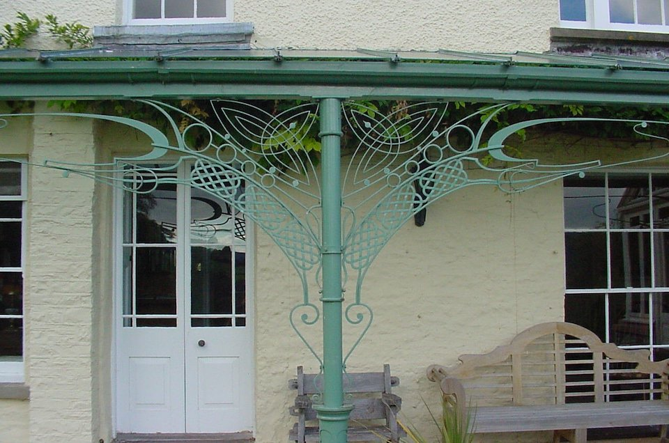 Ornate Metal Veranda with Victorian columns, Custom Celtic Dragon design brackets spandrels and a  Glazing Bar Roof canopy with glass panels only