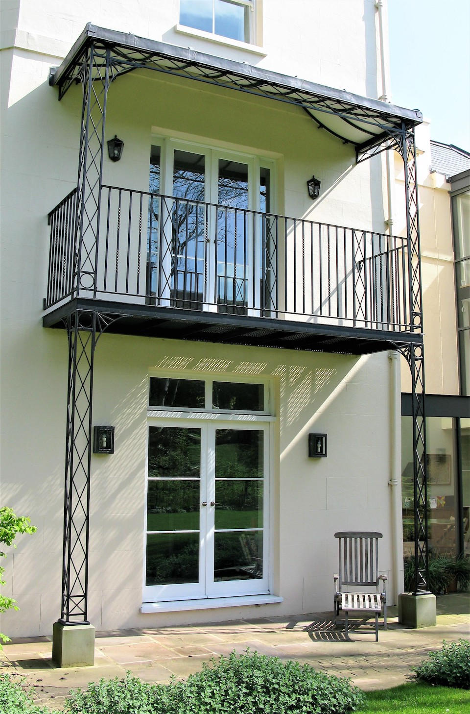 Traditionally made yet Modern Regency Ironwork Veranda Balcony with Matching Wrought Iron Railings and Floor Deck, Stone Plinths, Cast Shoe Covers, Spandrel Brackets and a Lined and Leaded Roof Frame Covering a Side Entrance and French Doors From a Master Bedroom
