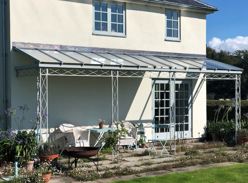 Trellis Style Regency Veranda Ironwork with a Straight Unhipped Glazing Bar Roof which has Glass Panels over French Doors and Zinc Galvanised Infill Sheets to created a shaded outdoor living space