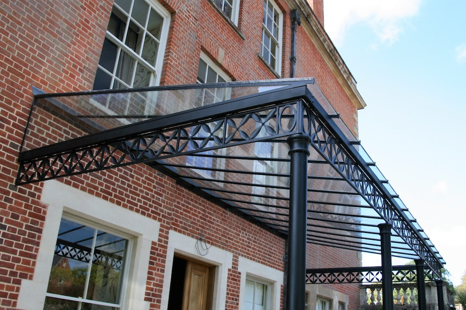 Traditional Wrought Iron Custom Column Veranda with flower, leaf design decorative deep Frieze panels and straight, un-hipped glazing bar roof frame , fully glazed with glass panels to triangular ends