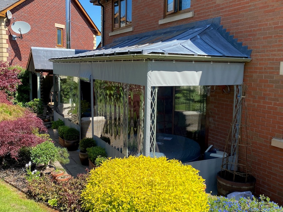Traditional Wrought Iron Trellis Style Veranda with Glazing bar roof which has glass panels over windows and zinc infill sheets, cast shoes and guttering, shown with a tailor made tarpaulin cover