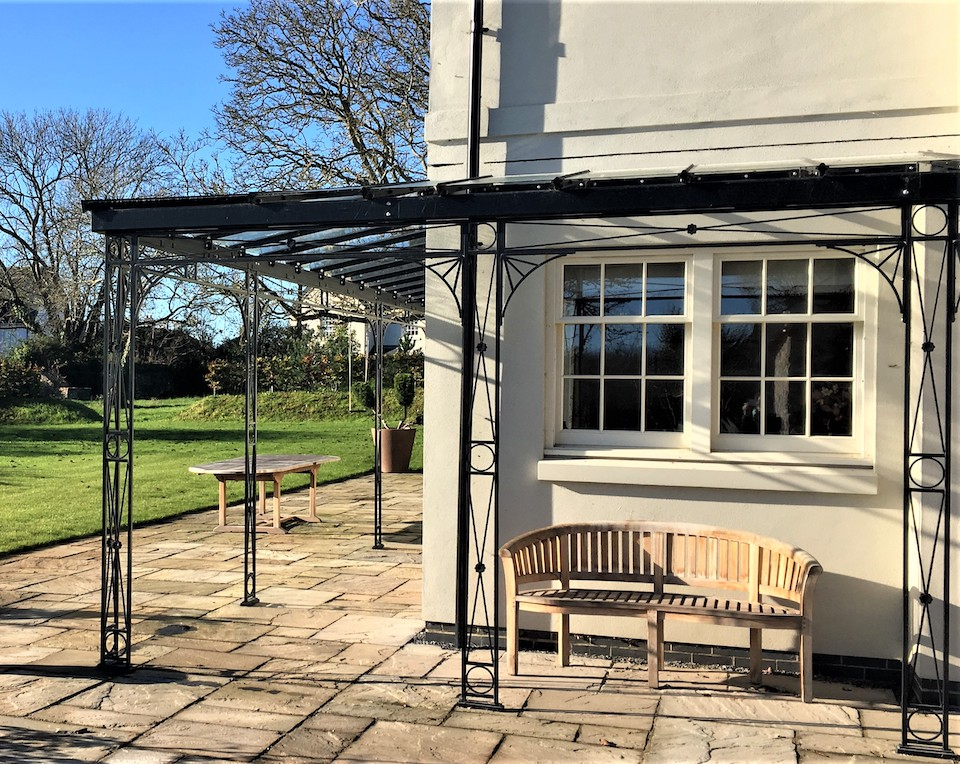 Decorative Traditional Style Hand Crafted Metal Wrap Around Veranda with Cast Iron Shoe Covers and Glazing Bar Roof Frame with Glass Panes Only creating a covered Walkway and Seating Area