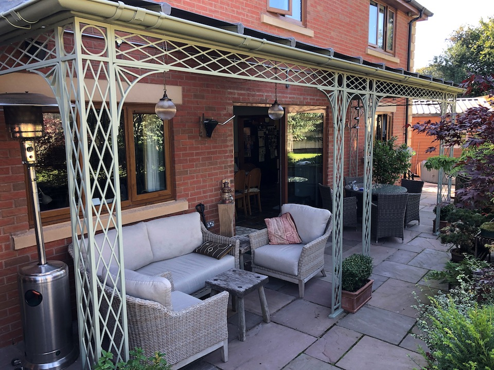 Traditional Trellis Verandah with Spandrel Brackets, Cast Shoe Covers and a curved Glazing Bar Roof Cover with Glass panes over Patio Doors and Windows and Zinc Infill sheets to the remainder creating a shaded outdoor living space