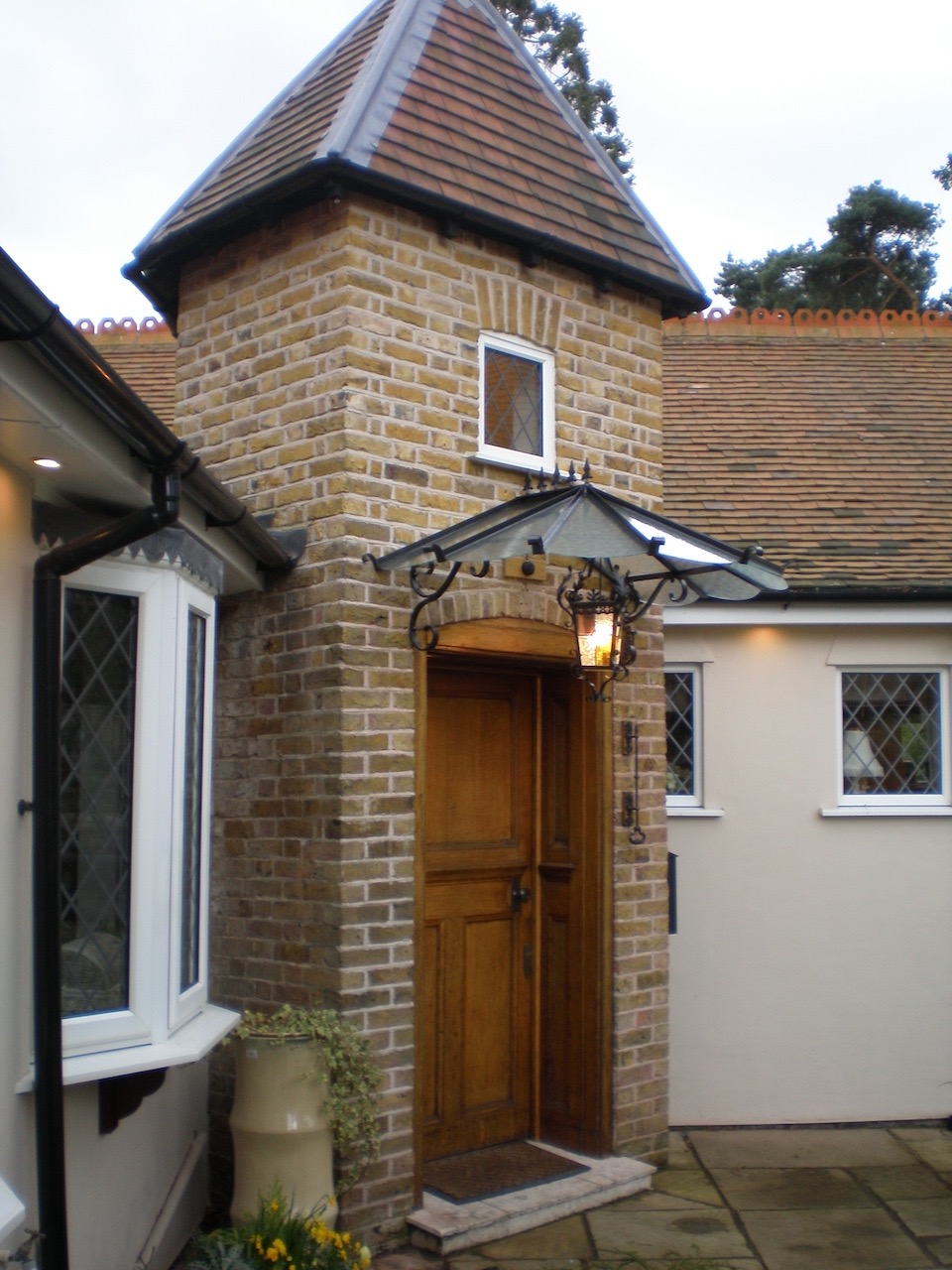 Traditional curved French style Scalloped Glass and metal Door cover Canopy with cast iron finial to the roof ridge and custom scroll spandrel brackets