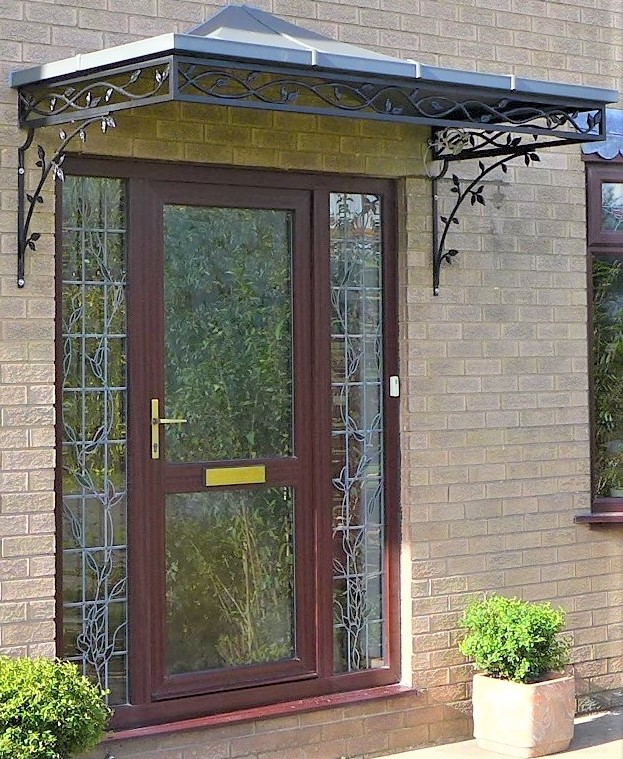 Double width traditional Wrought Iron Door Canopy with Cast Iron Organic roseleaf and vine design frieze panels and brackets finished with a complete zinc roof cover